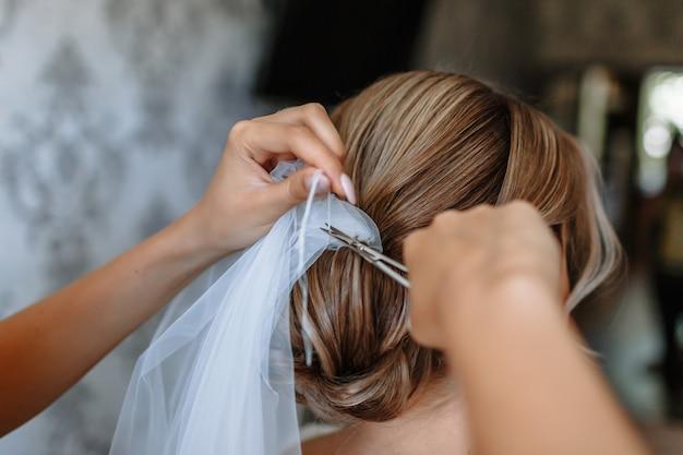 As mãos da menina cortam o fio que segura o véu do casamento