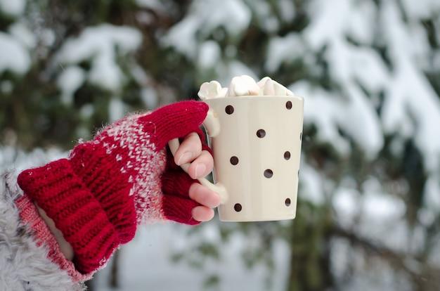 As mãos da menina em luvas sem dedos artesanais rosa, segurando um copo com marshmallow de café sobre fundo de neve do inverno. inverno e natal.
