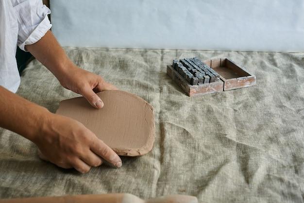 As mãos da menina estão segurando uma camada de argila sobre a mesa