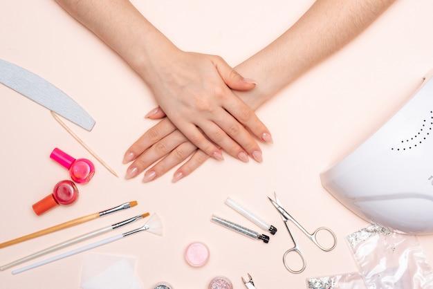 As mãos da menina no fundo de acessórios de manicure. fechar-se