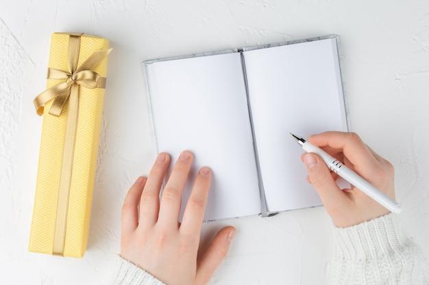 As mãos da menina seguram um caderno em branco entre a caixa de presente. metas, planos, sonhos, lista de tarefas