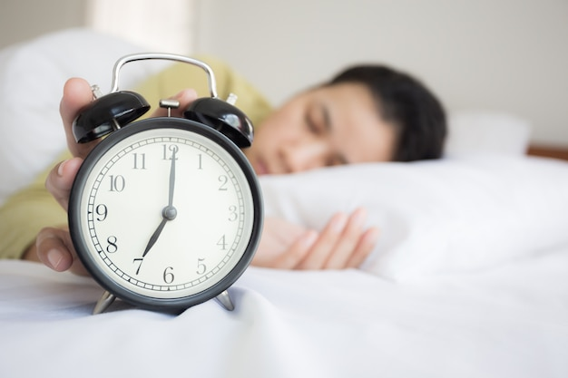 As mãos da mulher asiática estão fechando o despertador no quarto