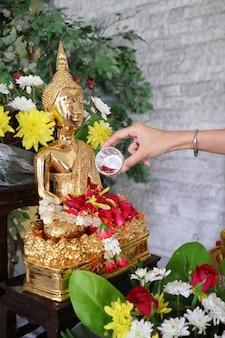 As mãos da mulher borrifam água em uma imagem de buda, um gesto de adoração durante o festival anual songkran. religião e feriado