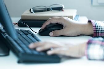 As mãos da mulher clicam no mouse do computador