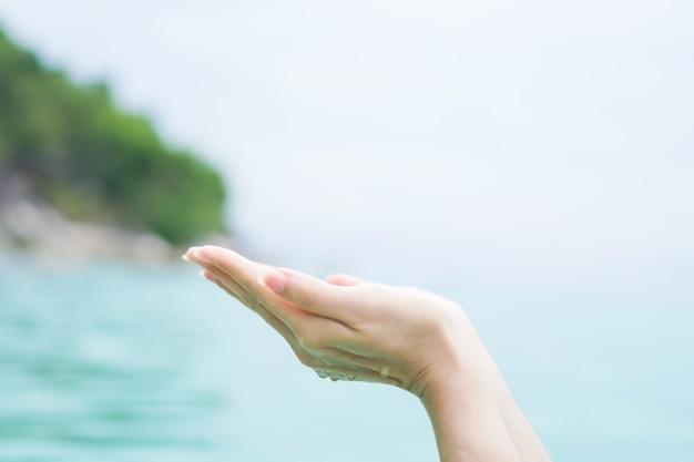 As mãos da mulher colocam juntas como rezar em frente à praia limpa da natureza e céu azul.