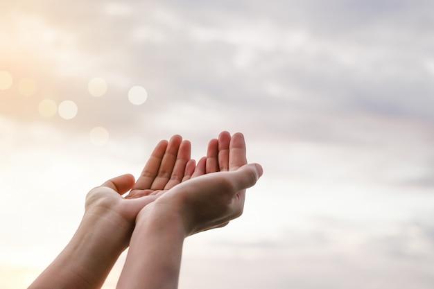 As mãos da mulher colocam junto como rezar na frente do fundo verde da natureza.