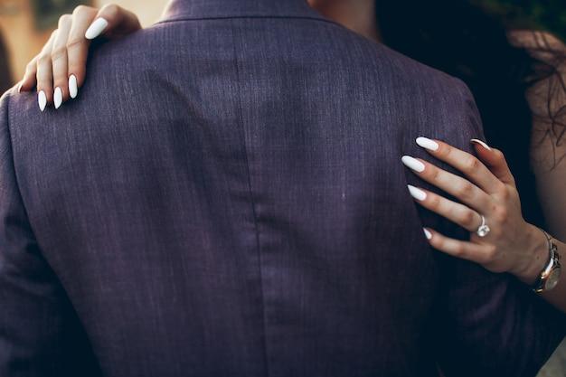 As mãos da mulher com as unhas brancas estão nas costas do homem