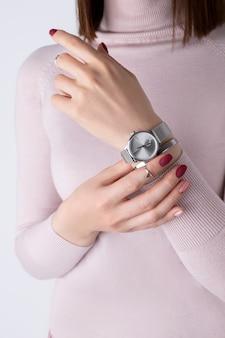 As mãos da mulher com jóias de prata e acessórios. menina com design de manicure primavera verão rosa mínimo.