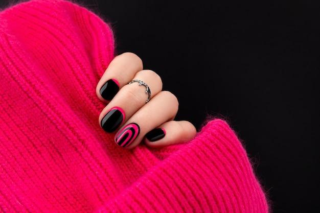 As mãos da mulher com manicure rosa e preta na moda segurando o chapéu.