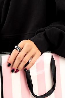 As mãos da mulher com manicure rosa e preta na moda segurando o saco de papel.