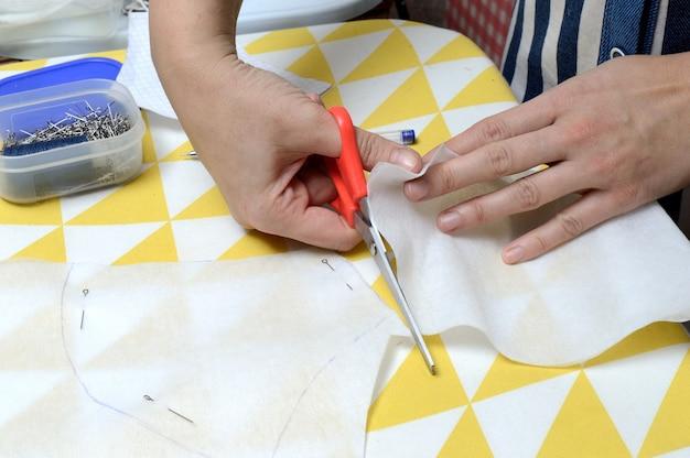 As mãos da mulher cortam o tecido com uma tesoura de acordo com o padrão na mesa.