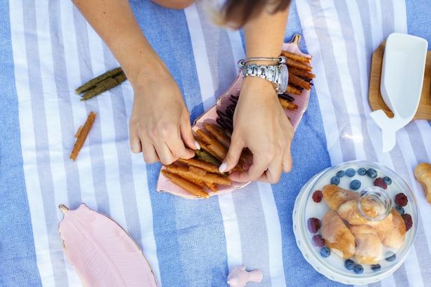 As mãos da mulher da vista superior tomam o rolo do pastillum da bandeja. piquenique de verão