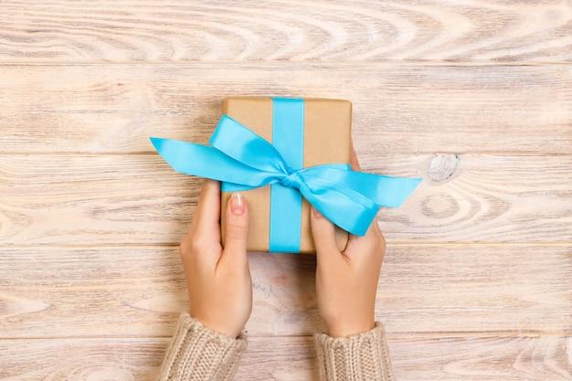 As mãos da mulher dão o valentim envolvido ou o outro presente feito a mão do feriado no papel com fita azul.
