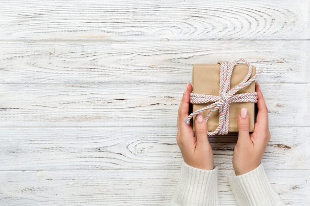 As mãos da mulher dão o valentim envolvido ou o outro presente feito a mão do feriado no papel com fita cor-de-rosa.