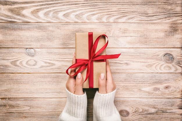 As mãos da mulher dão o valentim envolvido ou o outro presente feito a mão do feriado no papel com fita vermelha.