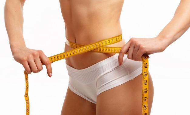 As mãos da mulher de medição da cintura