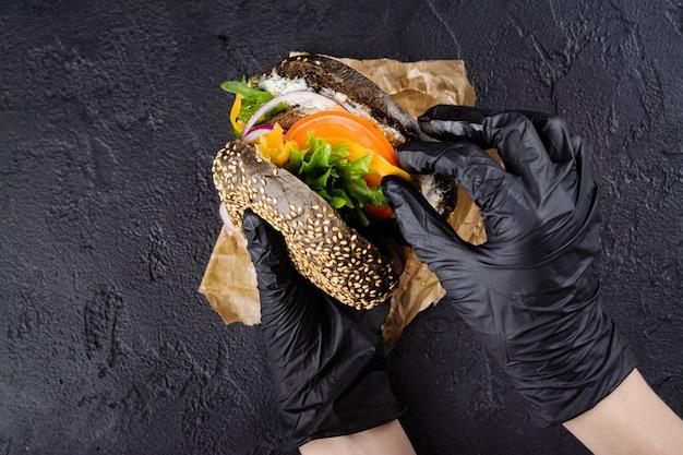 As mãos da mulher em luvas de borracha pretas estão segurando suculento hambúrguer de pão preto