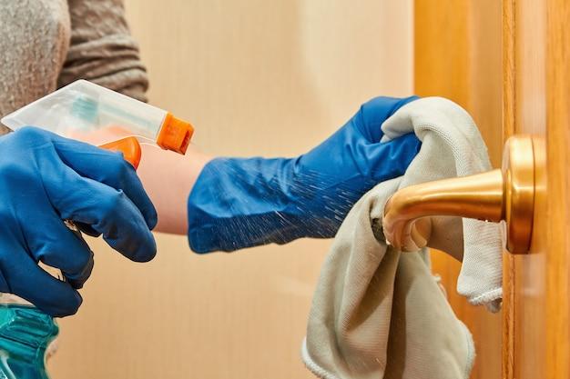 As mãos da mulher em luvas de proteção azuis usando pano de limpeza e spray de detergente estão limpando a maçaneta da porta para proteção contra vírus e covid-19.