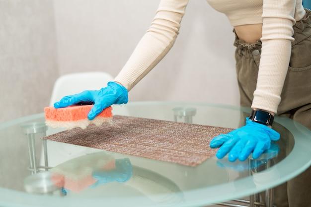 As mãos da mulher em luvas limpam a mesa com uma esponja