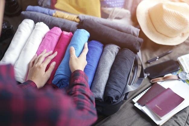 As mãos da mulher embandeiram a roupa no saco da mala de viagem na cama, preparam-se para a viagem nova e viajam-se ao fim de semana longo.