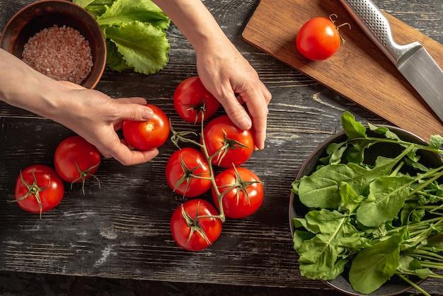 As mãos da mulher estão arrancando um tomate vermelho maduro de um galho