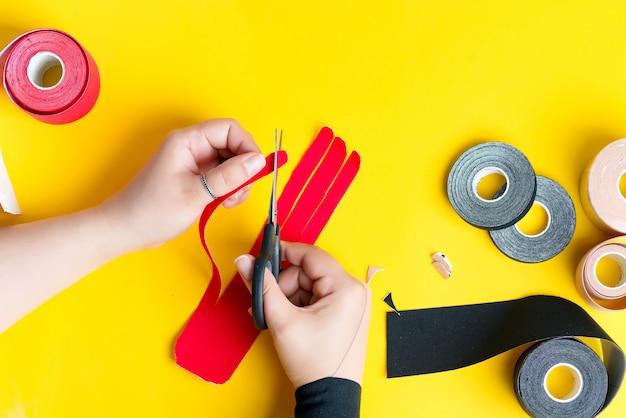 As mãos da mulher estão cortando fitas vermelhas para o tratamento de cinesiotapia