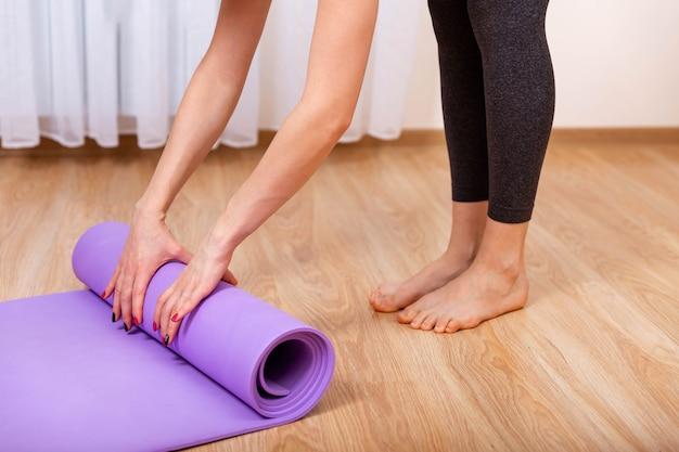 As mãos da mulher estão enrolando o tapete de exercícios e se preparando para fazer ioga em casa