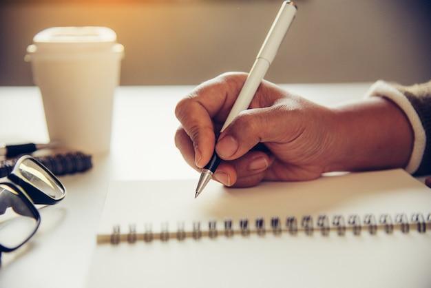 As mãos da mulher estão escrevendo nota e xícara de café em aberto spect e luz ouro na manhã