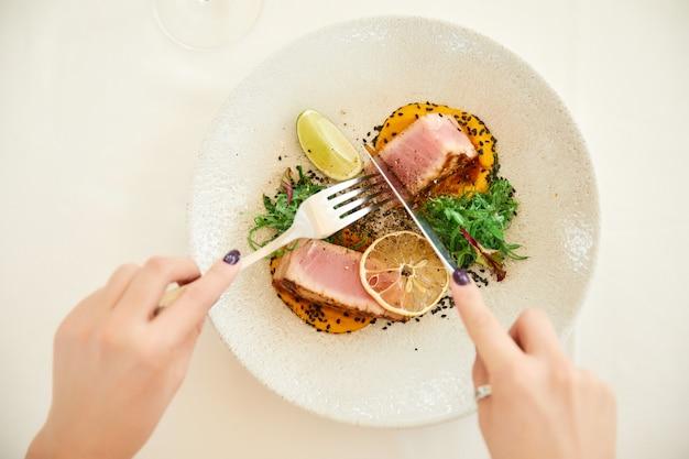 As mãos da mulher estão segurando talheres sobre um prato de atum