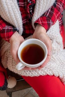 As mãos da mulher estão segurando uma xícara branca de chá ou café vestida com roupas festivas vermelhas e brancas
