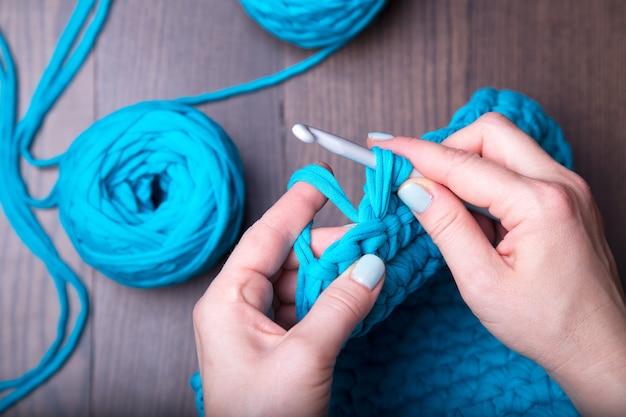 As mãos da mulher estão tricotando na superfície de madeira