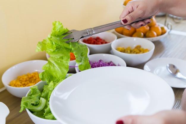 As mãos da mulher estão usando o vegetal verde do aperto do tong à placa branca.
