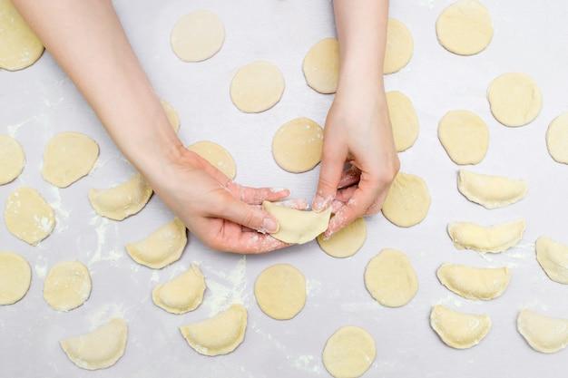 As mãos da mulher fazem ravioli