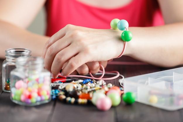As mãos da mulher fazendo bracelete com contas de plástico