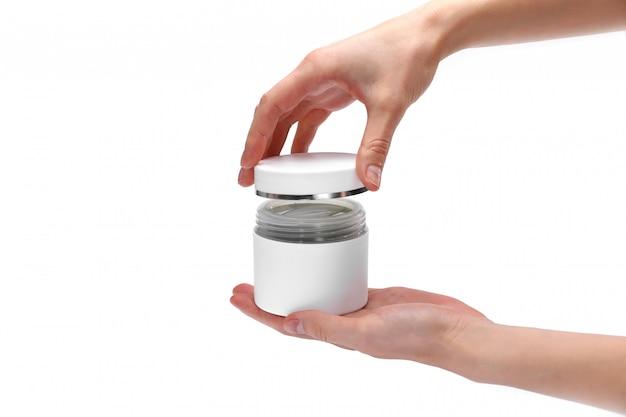 As mãos da mulher, garota segurando um frasco aberto de creme, close-up, parede branca, copie o espaço, para texto, vista superior.
