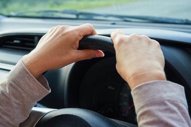As mãos da mulher no volante, o motorista está dirigindo o carro.