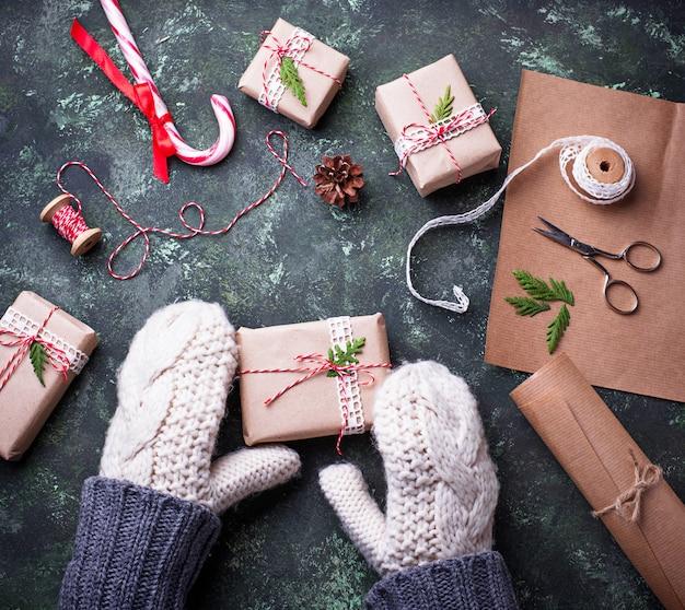 As mãos da mulher nos mitenes que embalam caixas com presentes dos presentes do natal. vista do topo