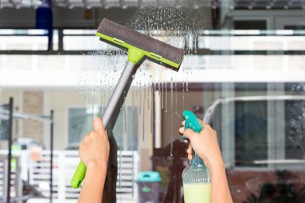 As mãos da mulher nova limpam o vidro com um vidro limpam-passatempos e conceitos do lazer.
