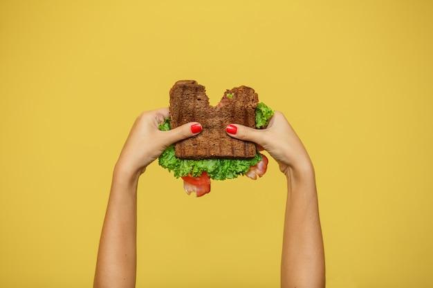 As mãos da mulher prendem o sanduíche mordido no fundo amarelo. conceito de promoção de sanduíche