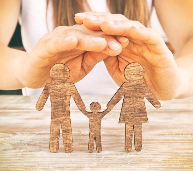 As mãos da mulher protegem as estatuetas de madeira da mãe, do pai e do filho na mesa de madeira