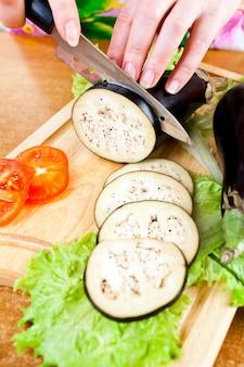 As mãos da mulher que cortam a beringela da beringela, atrás dos legumes frescos.