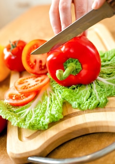 As mãos da mulher que cortam o pimentão de tomate, atrás dos legumes frescos.