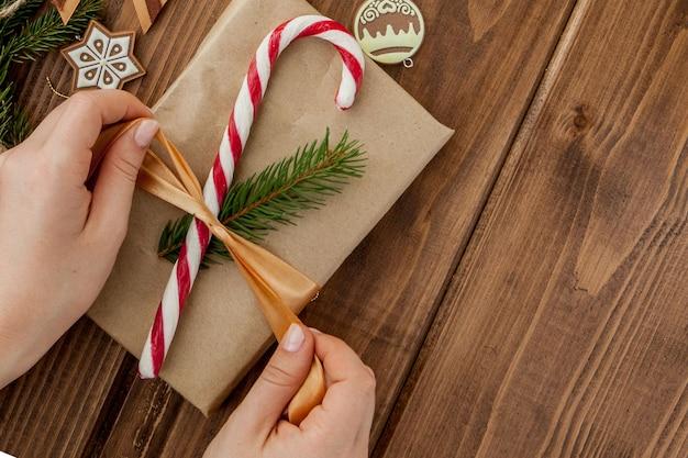 As mãos da mulher que envolvem o presente do natal, fim acima. presentes de natal despreparados em madeira com elementos de decoração e itens, vista superior. embalagem de natal ou ano novo diy.