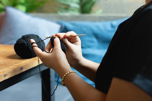 As mãos da mulher que fazem malha fazem crochê o relaxamento no café.