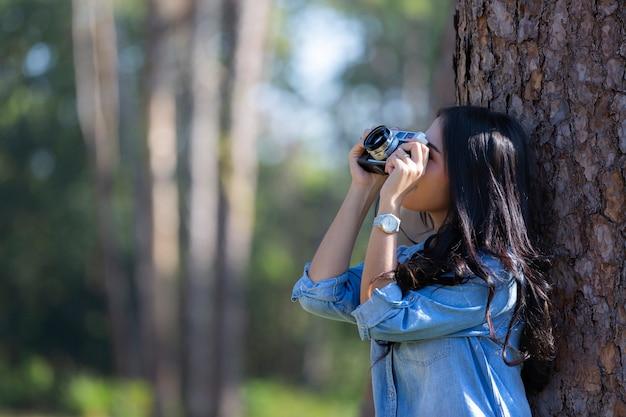 As mãos da mulher que guardam a câmera e que agarram fotos escondidas na madeira de pinho.