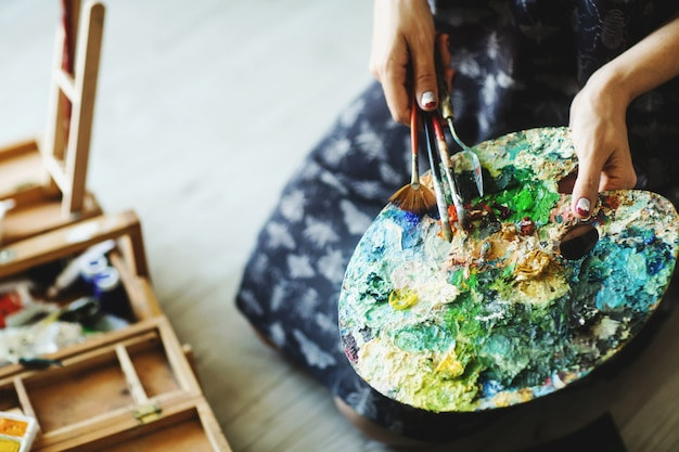 As mãos da mulher que guardam o pincel e a paleta com pinturas de óleo. fechar-se. conceito de arte
