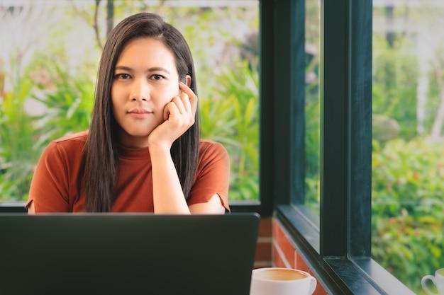 As mãos da mulher que pensam ao trabalhar no portátil olham a câmera. mulher que trabalha no escritório com café
