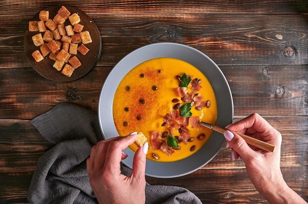 As mãos da mulher seguram crouton e colher com a tradicional sopa de creme de purê de abóbora com cebola e cenoura