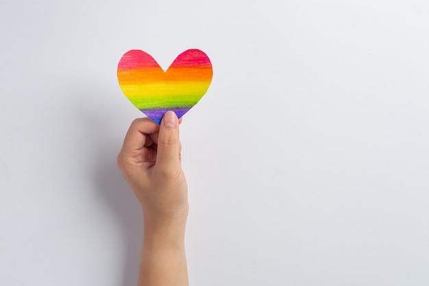 As mãos da mulher seguram o coração do arco-íris para o conceito de orgulho da comunidade lgbt