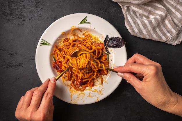 As mãos da mulher seguram um garfo e uma colher com uma pasta com tomate e pesto, foco seletivo, close-up, vista de cima